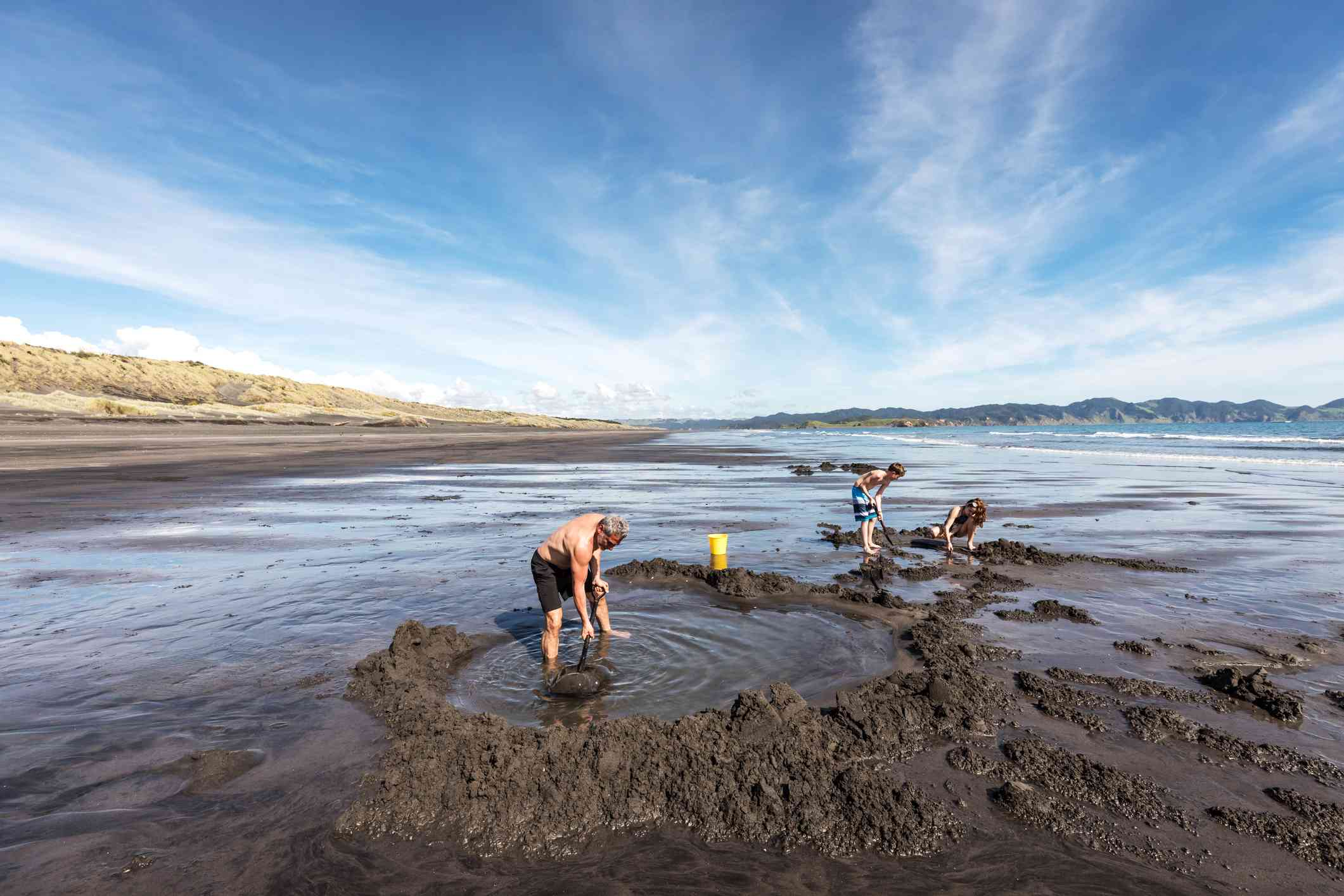 three people digging pools into dark sand
