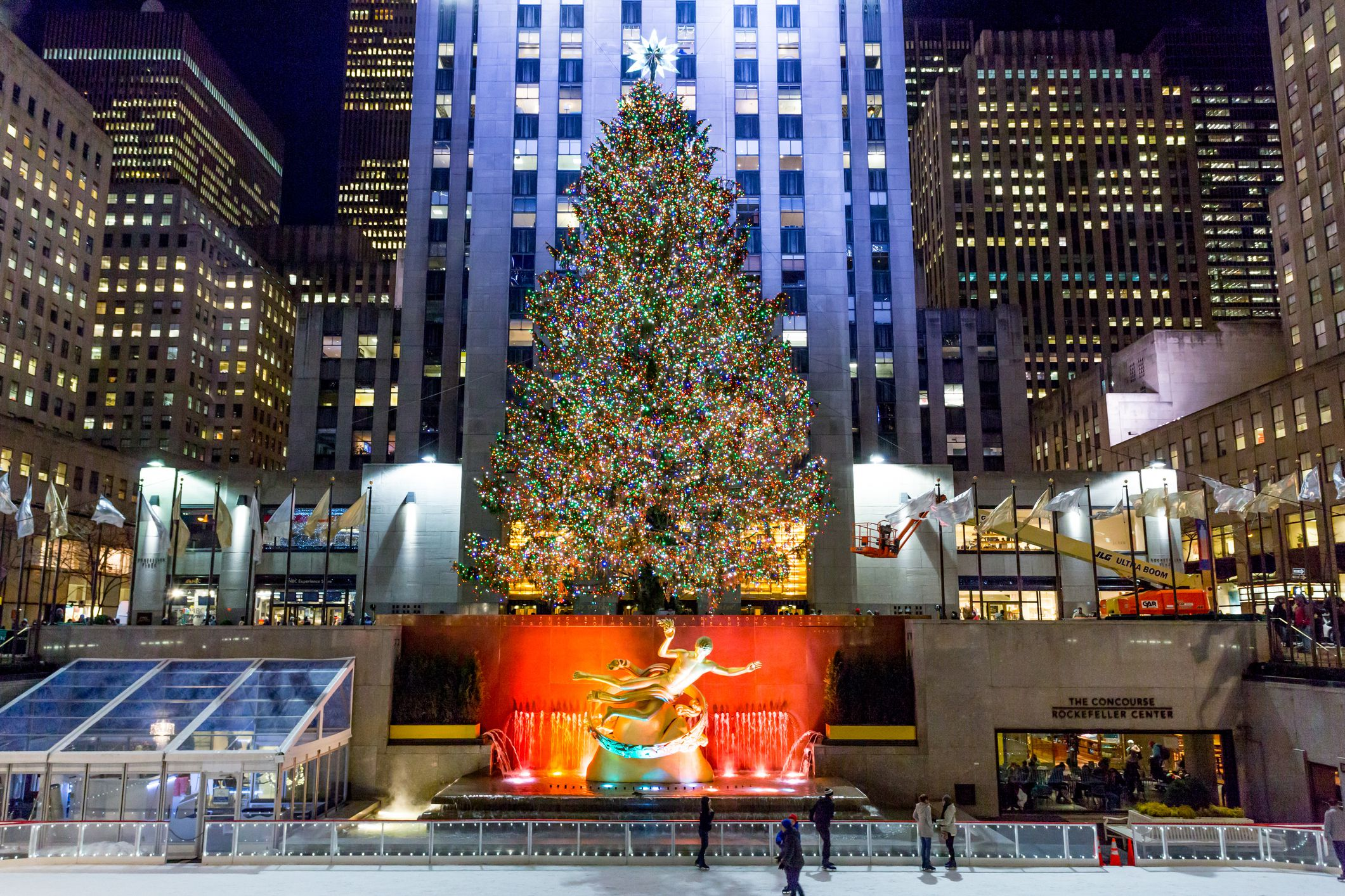 Brightly illuminated the Rockefeller Plaza ice skating rink filled with tourists and locals skating and watching, with a Christmas tree during the holiday season.