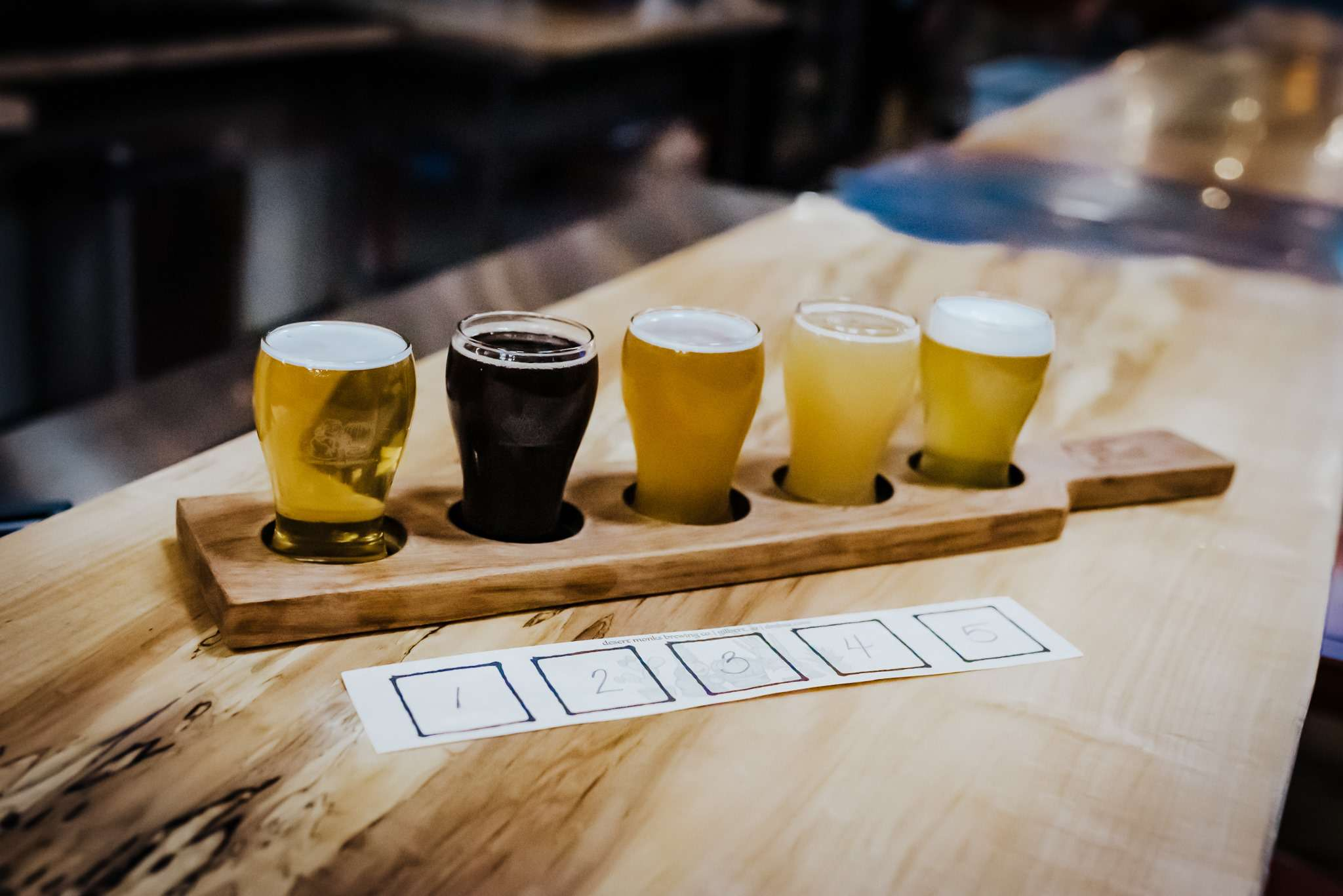 A flight of beer all different colors. A piece of paper numbering them lies in front of the flight