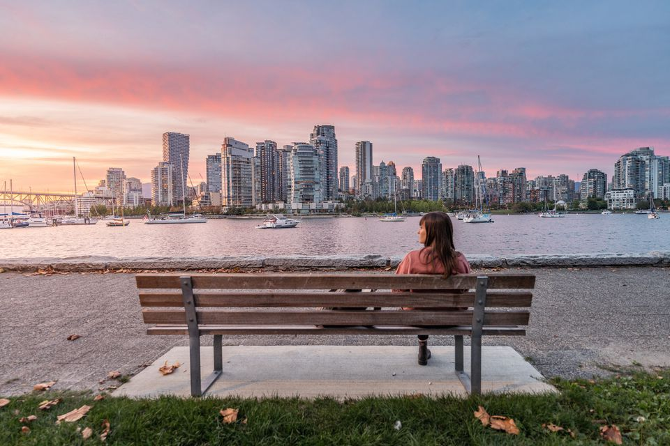 Woman sitting on a bench looking at Vancouver skyline, sunset from from the Island Park Walk. British Columbia, Canada