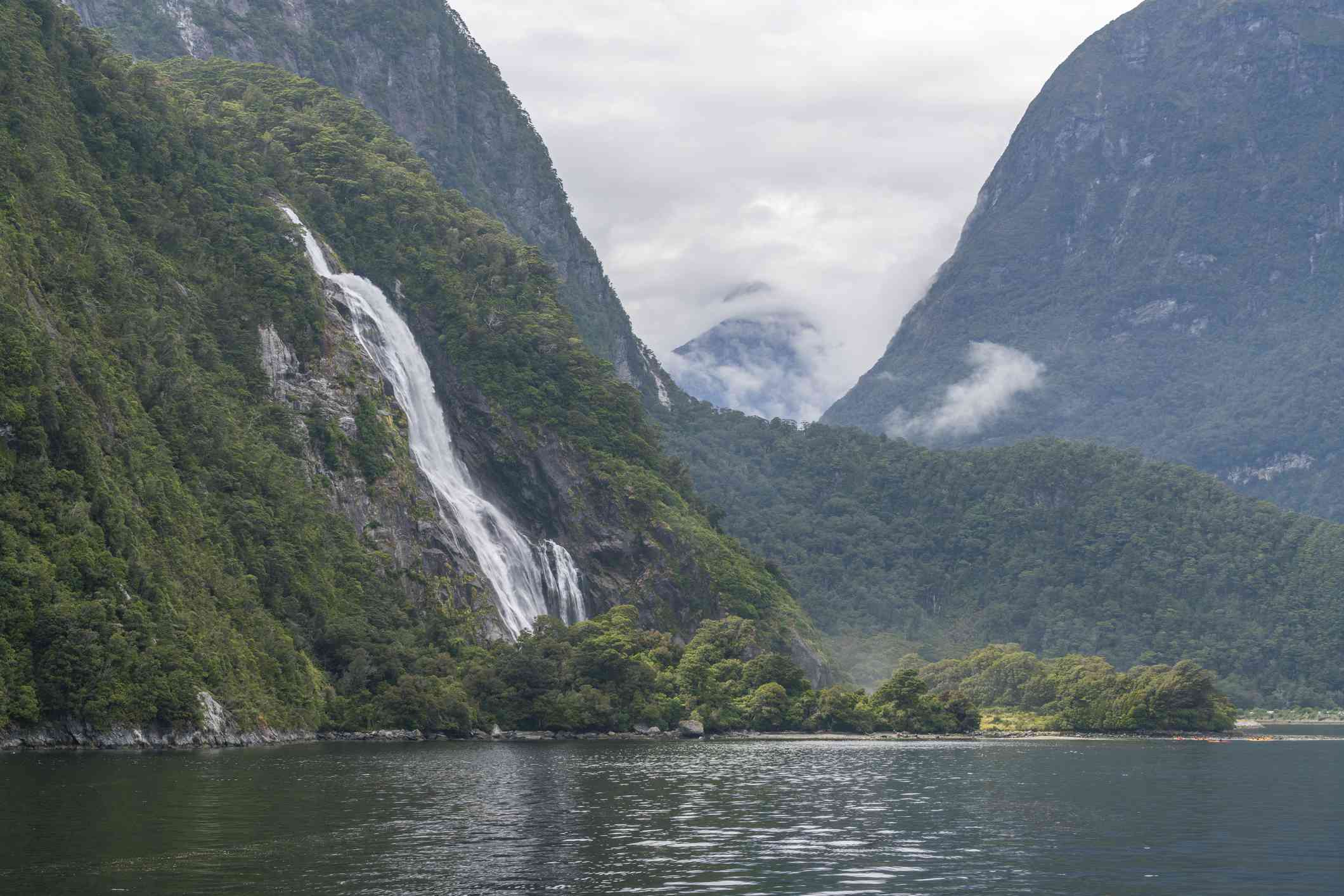 waterfalls flowing down high forested mountains