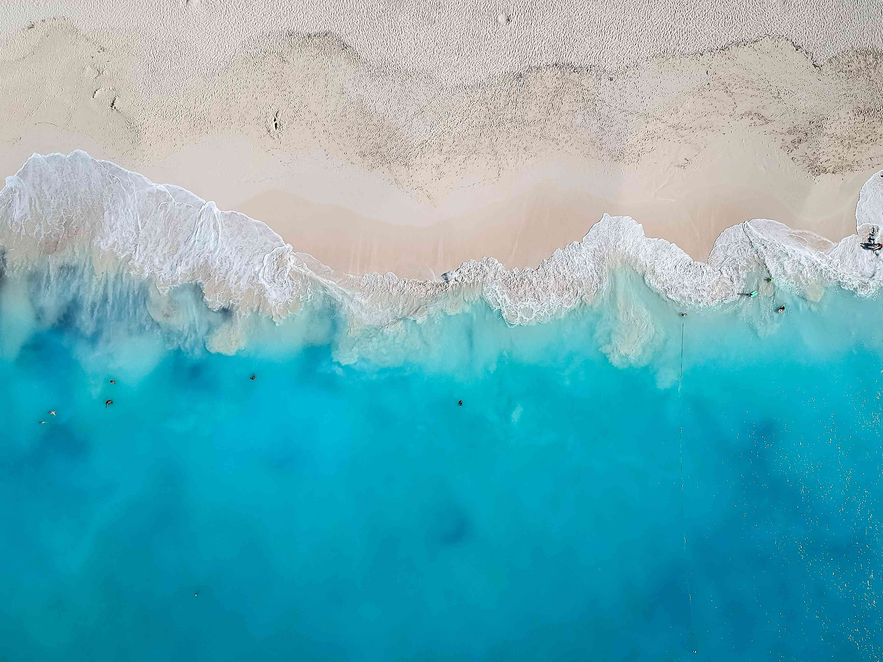 Aerial view of cerulean waves crashing on a white sand beach