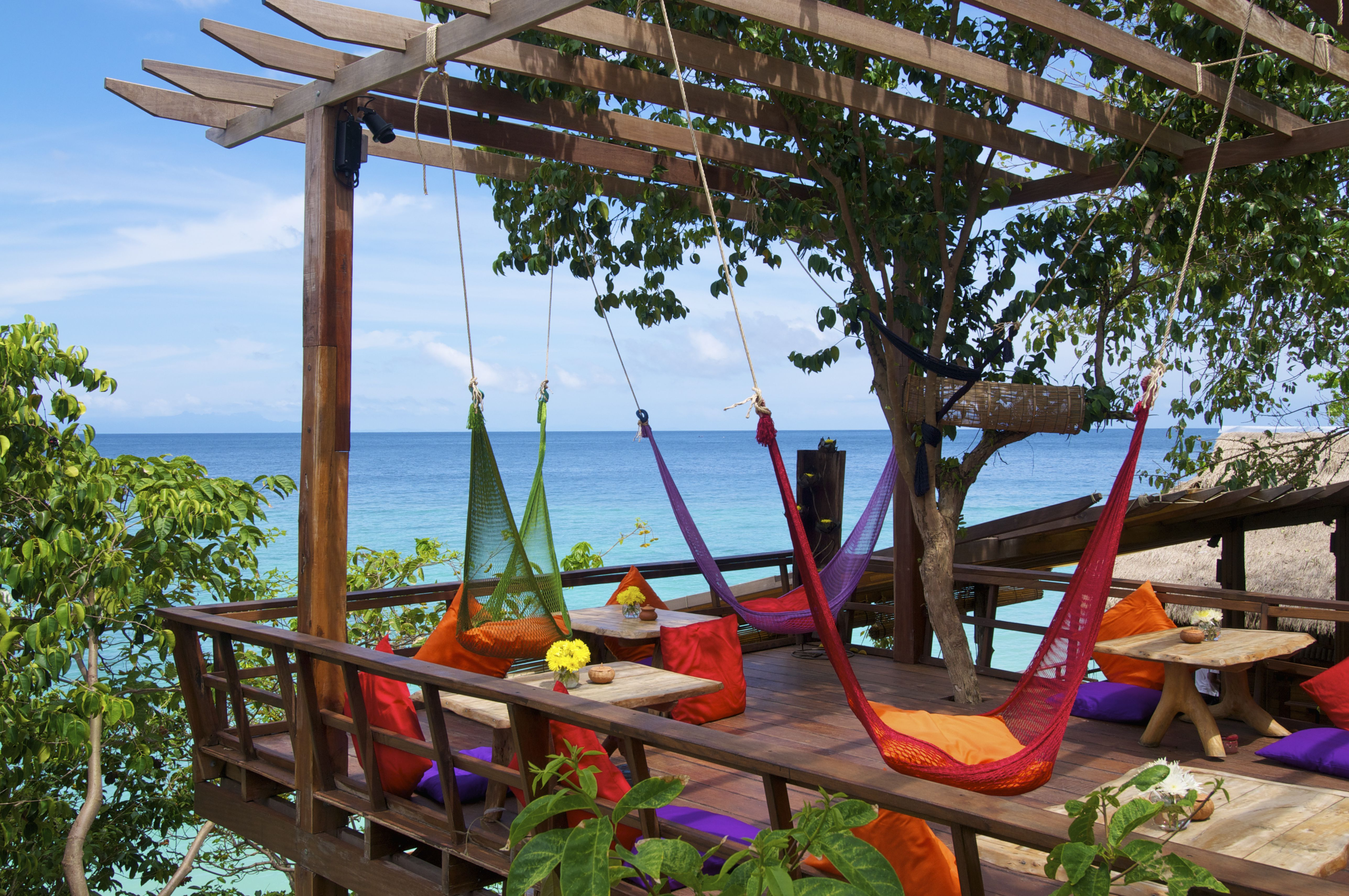 Colorful hammocks hang in a restaurant by the sea