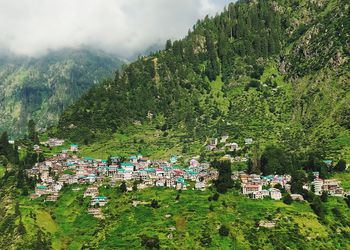 houses dotted on a steep green hillside with clouds