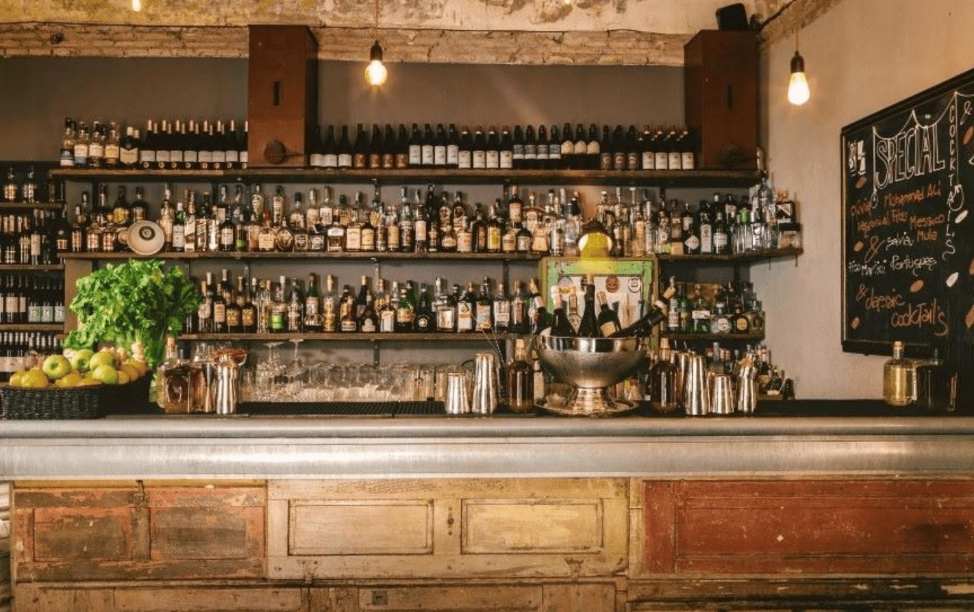 Wooden bar with various liquor bottles on shelves in bar del fico in Rome