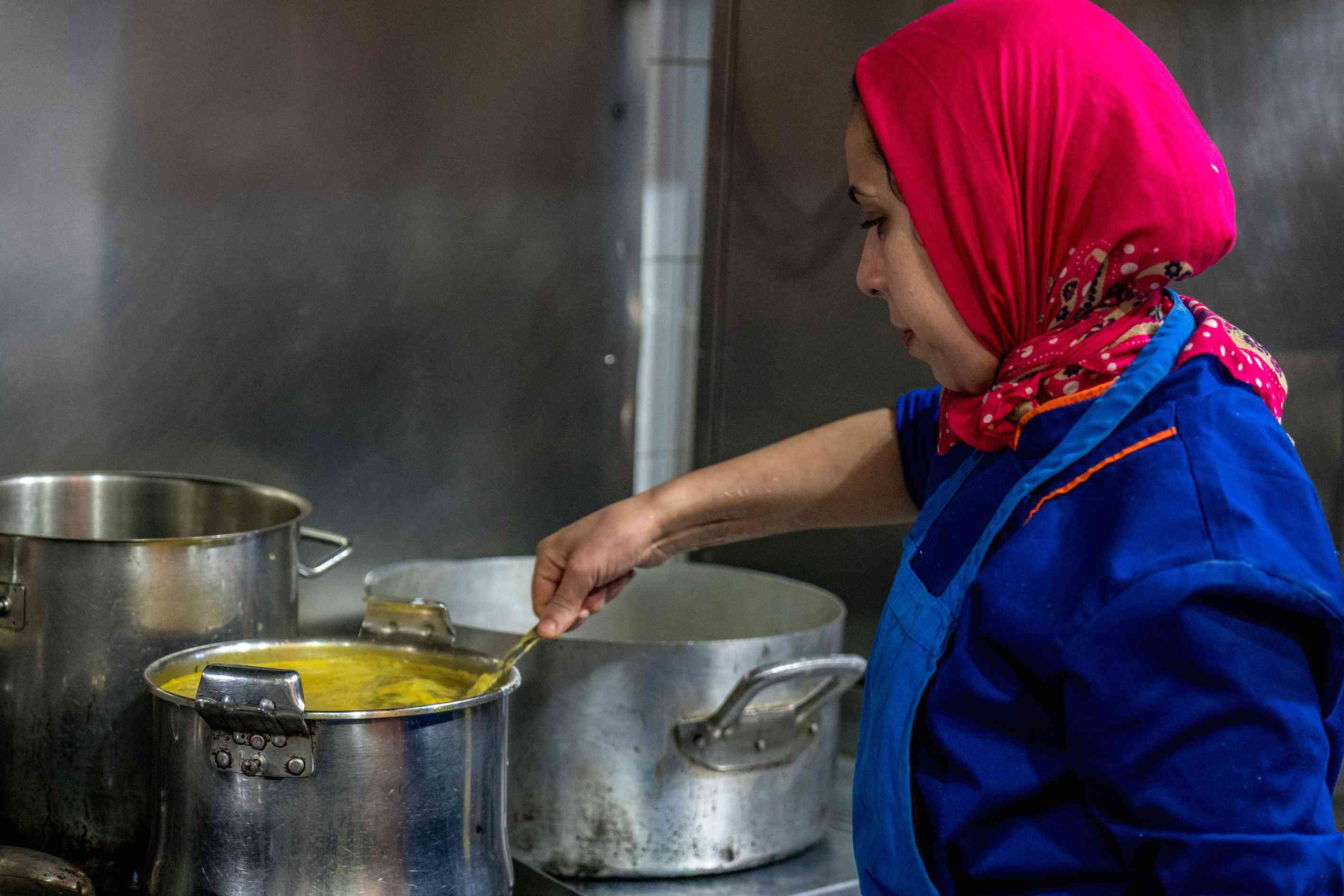 Moroccan lady stirring a cooking pot