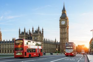 red double-decker busses driving traffic on Westminster Bridge with Big Ben in the background