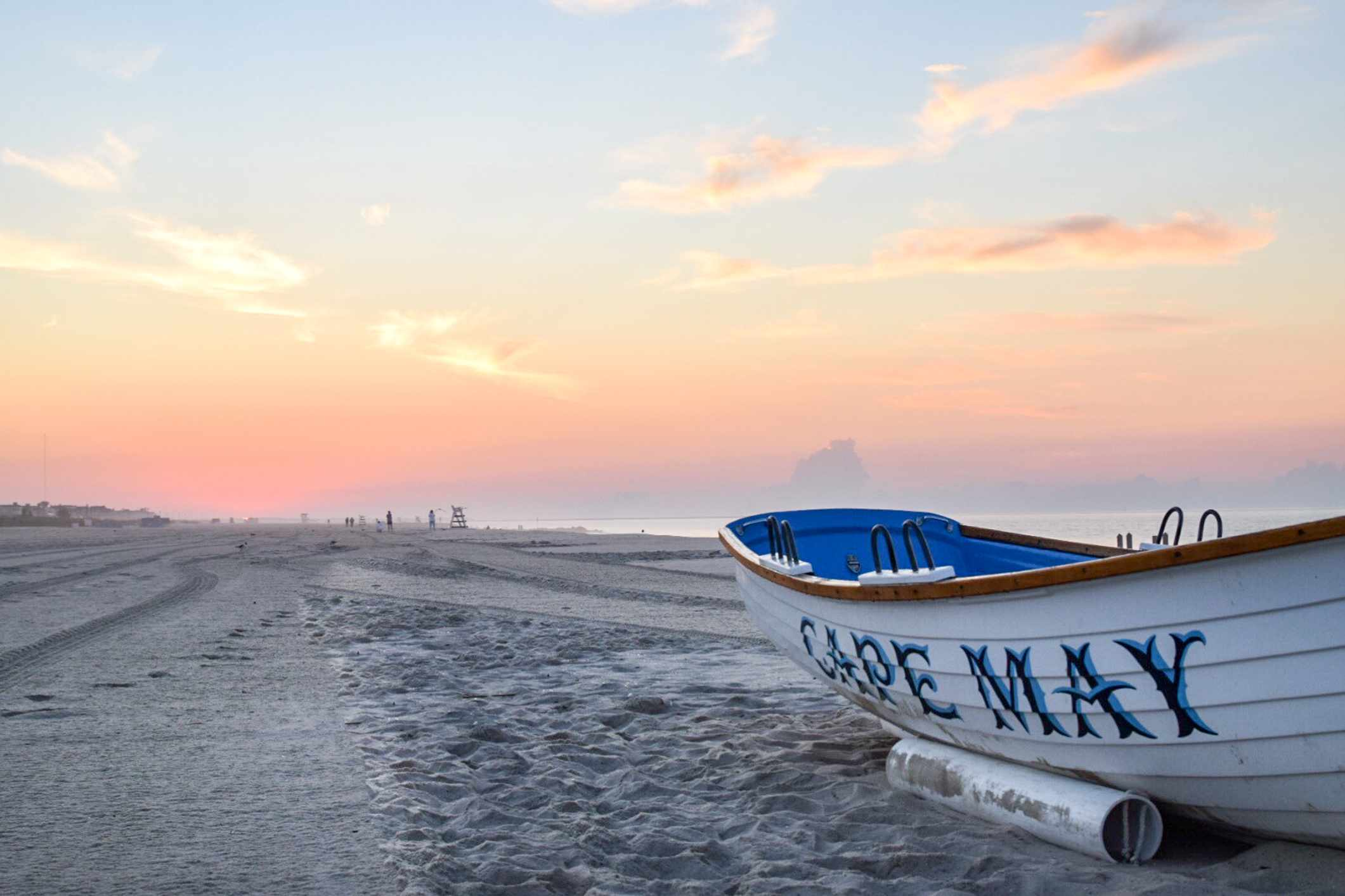 A boat with Cape May written on it on the beach