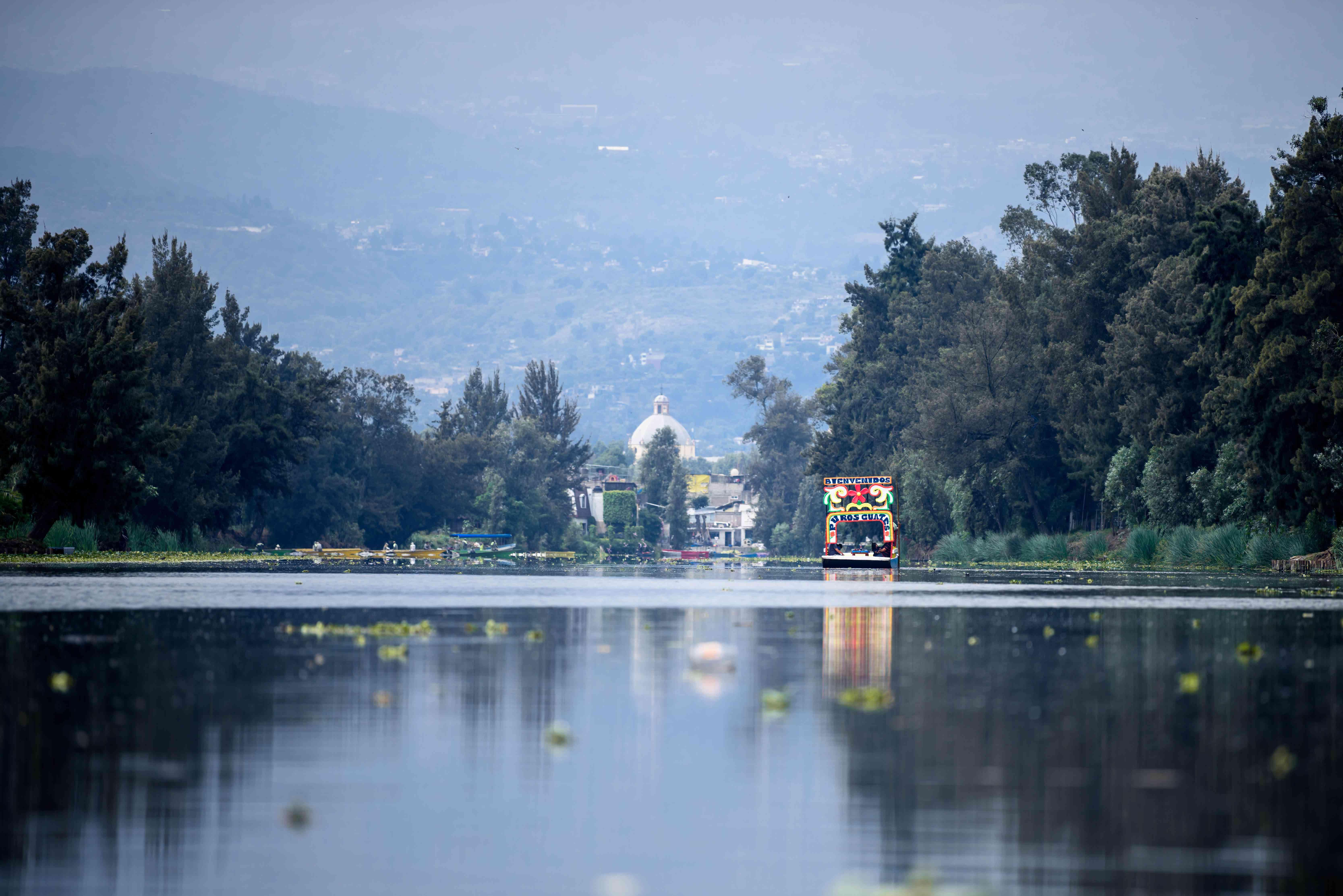 a colorful boat glides down the river in xochimilco