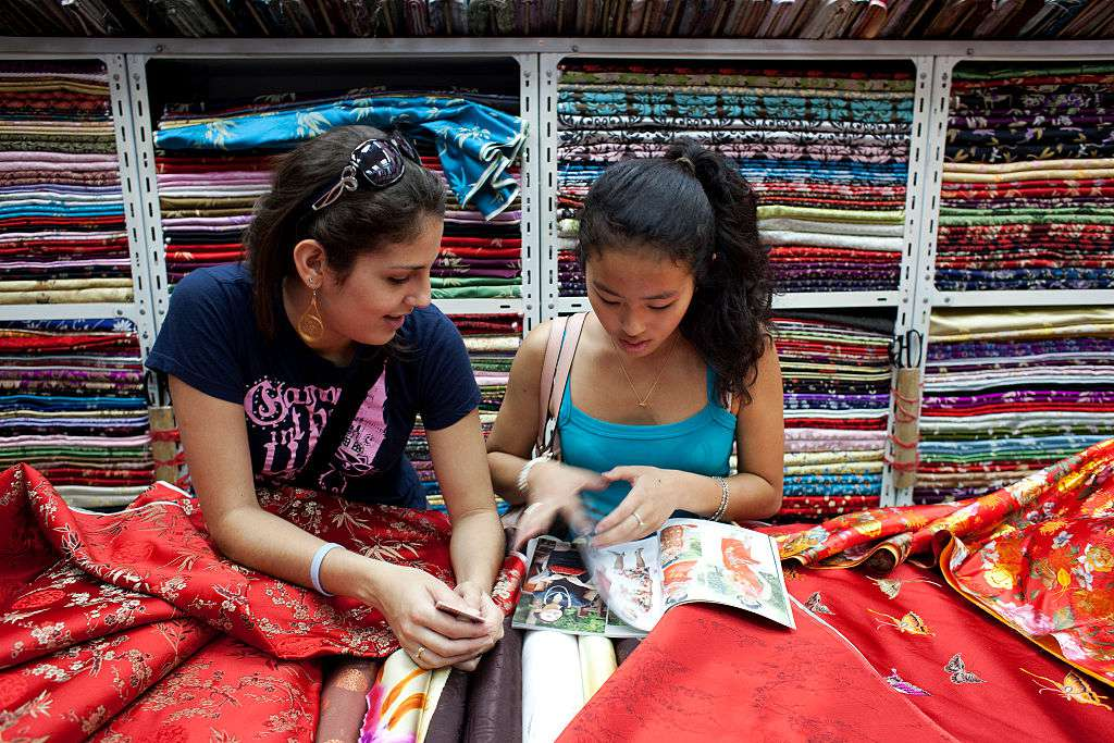 Tourists shop for dresses in the South Bund Fabric Market, famous for fabrics and cutting suits, in Shanghai, China