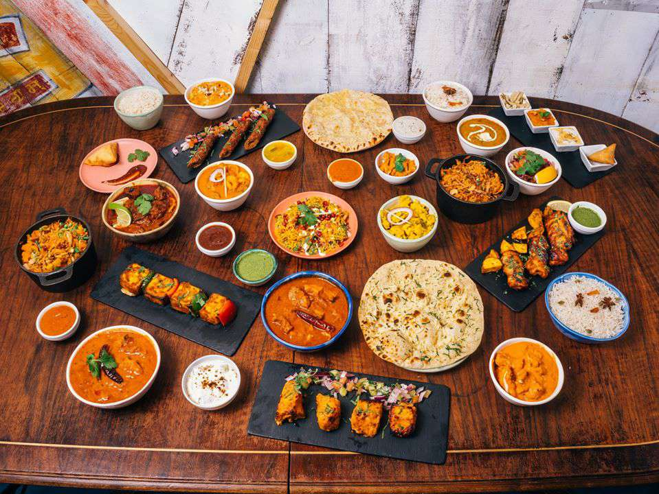Table at Chutnify filled with South Indian food