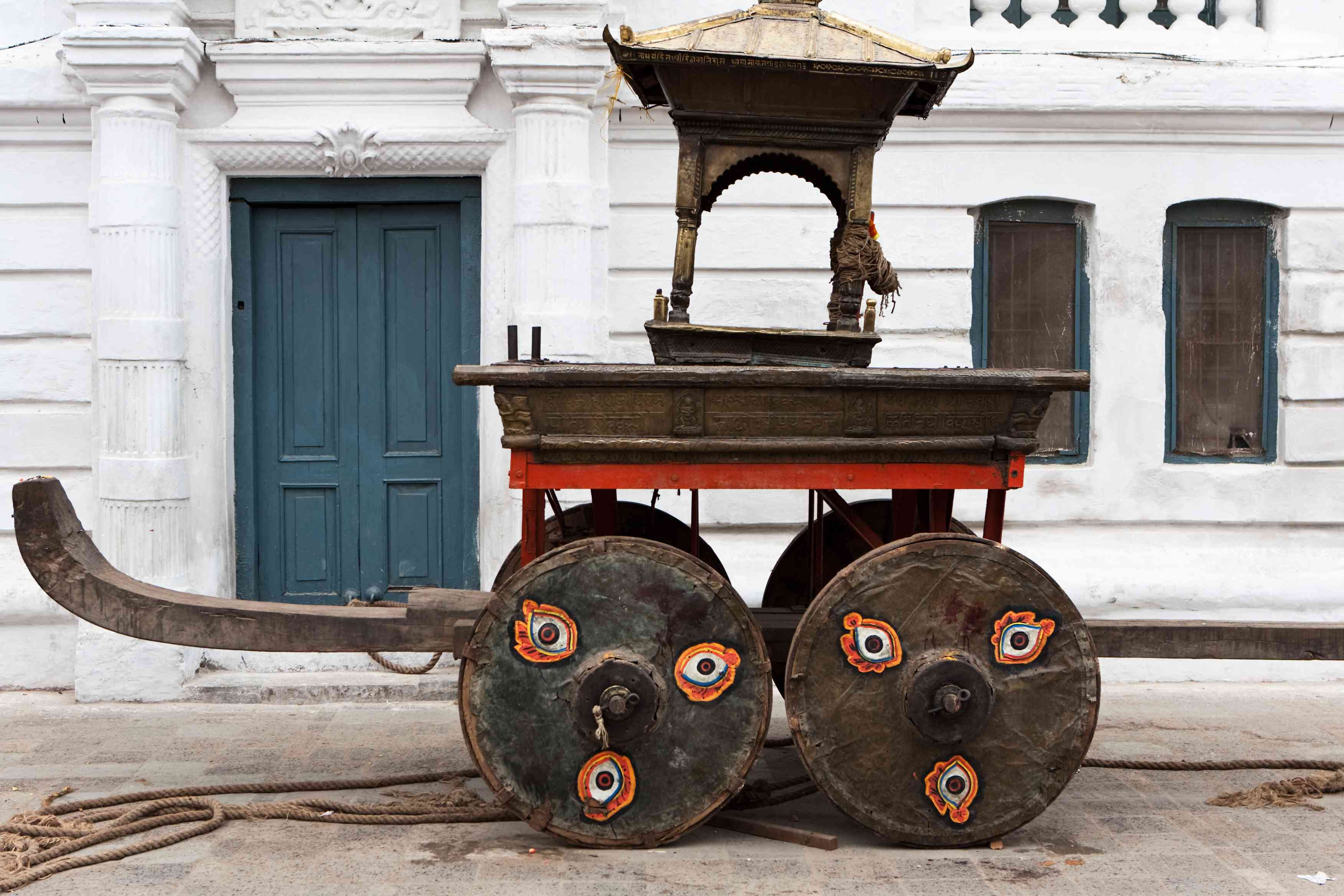 wooden chariot in front of a white palace building