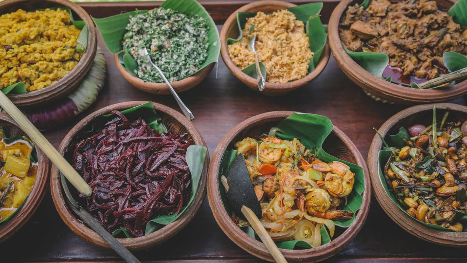 Clay bowls with banana leaves and various Sri Lankan foods on top of the leaves with serving spoons
