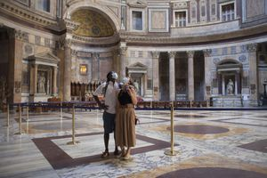 Couple enjoying the empty Pantheon in Rome, wearing protective face masks during COVID-19 pandemic