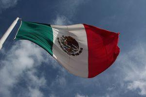 A giant Mexican flag flies against a blue sky