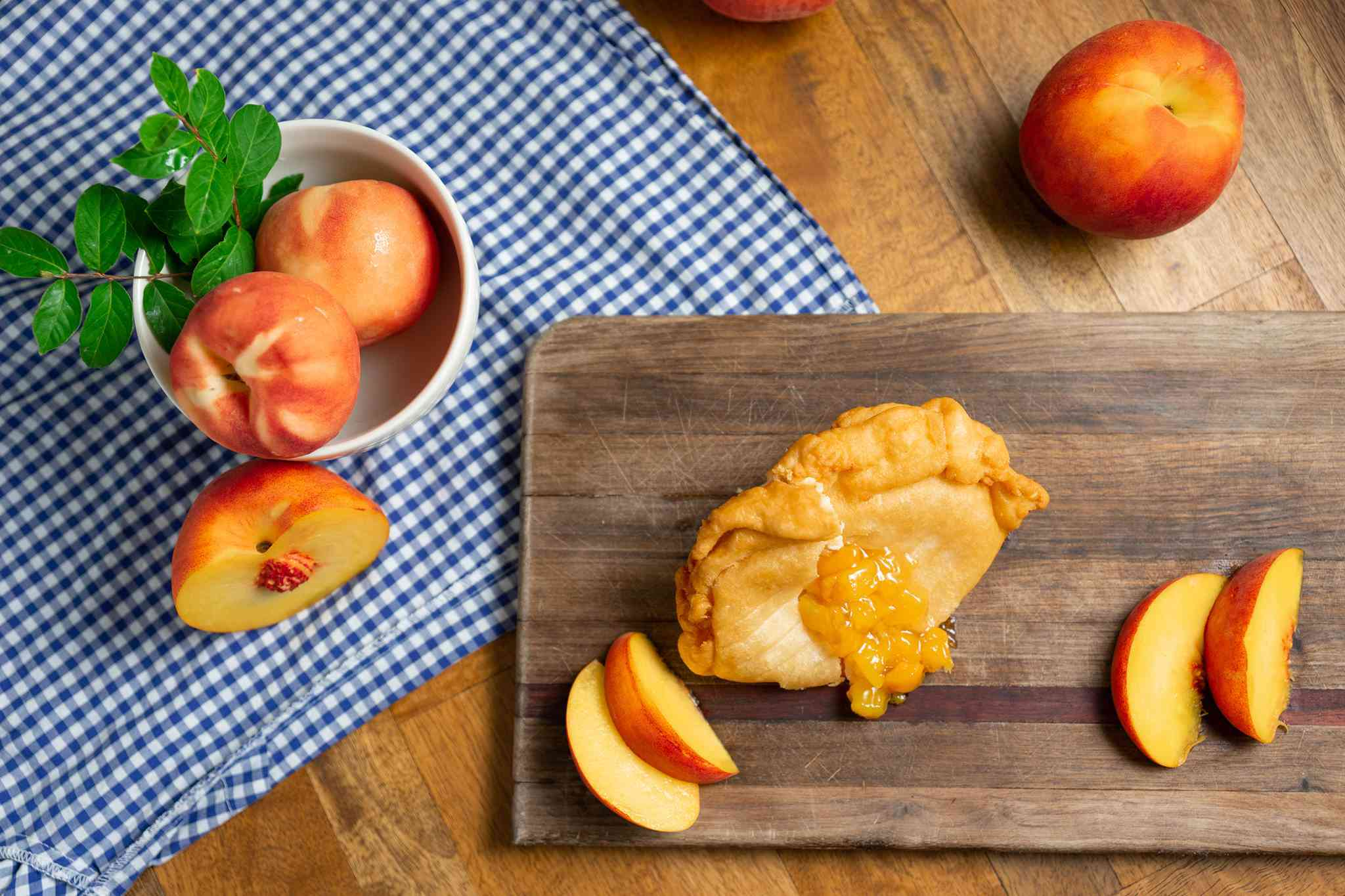 fried hand pie with peach filling coming out on a cutting board and table with sliced and whole peaches