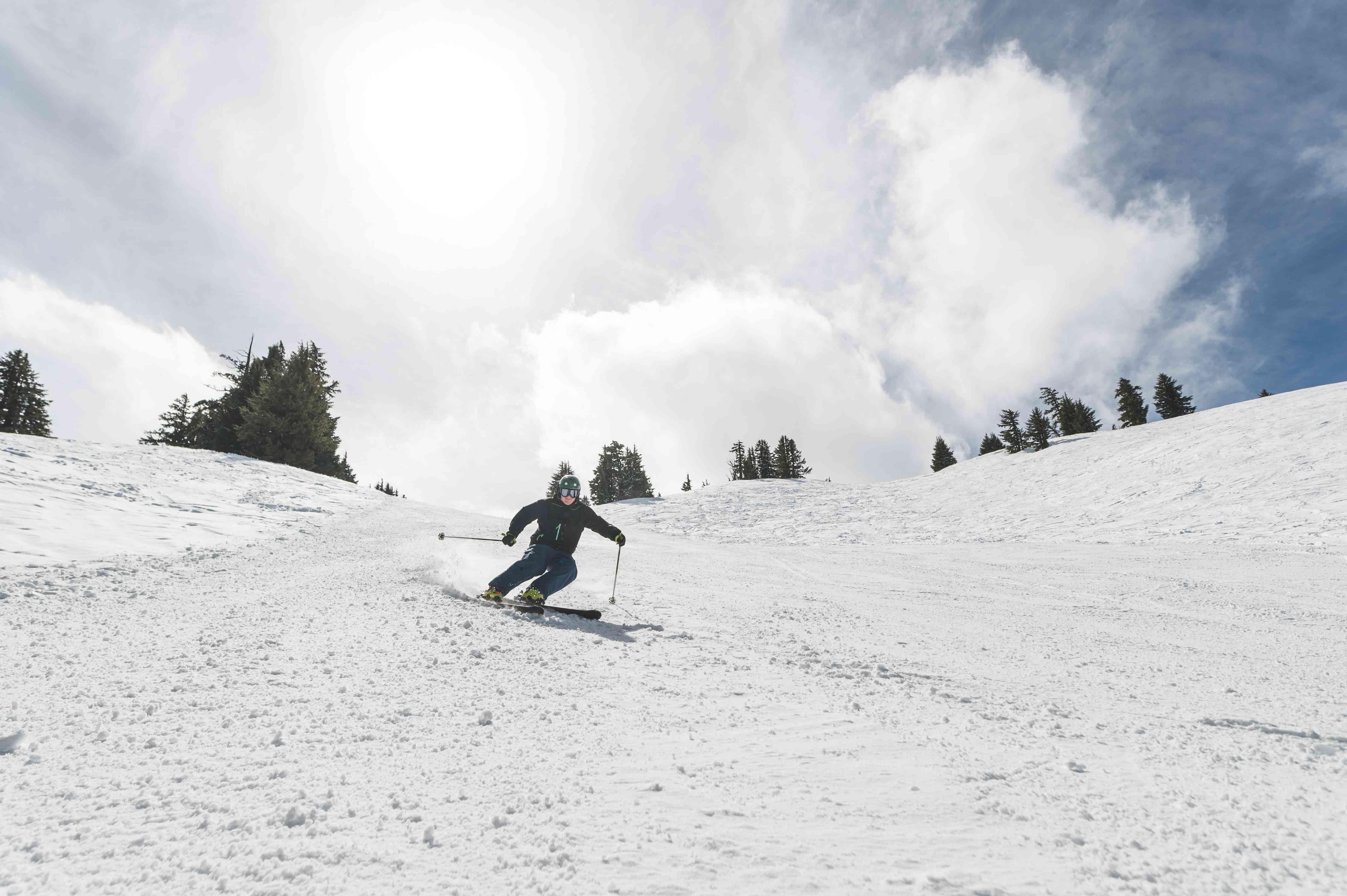 Male skiier racing down snow covered slope on a sunny afternoon.