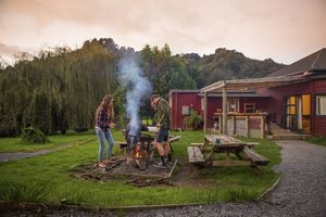 A couple starts a bonfire at the campsite.