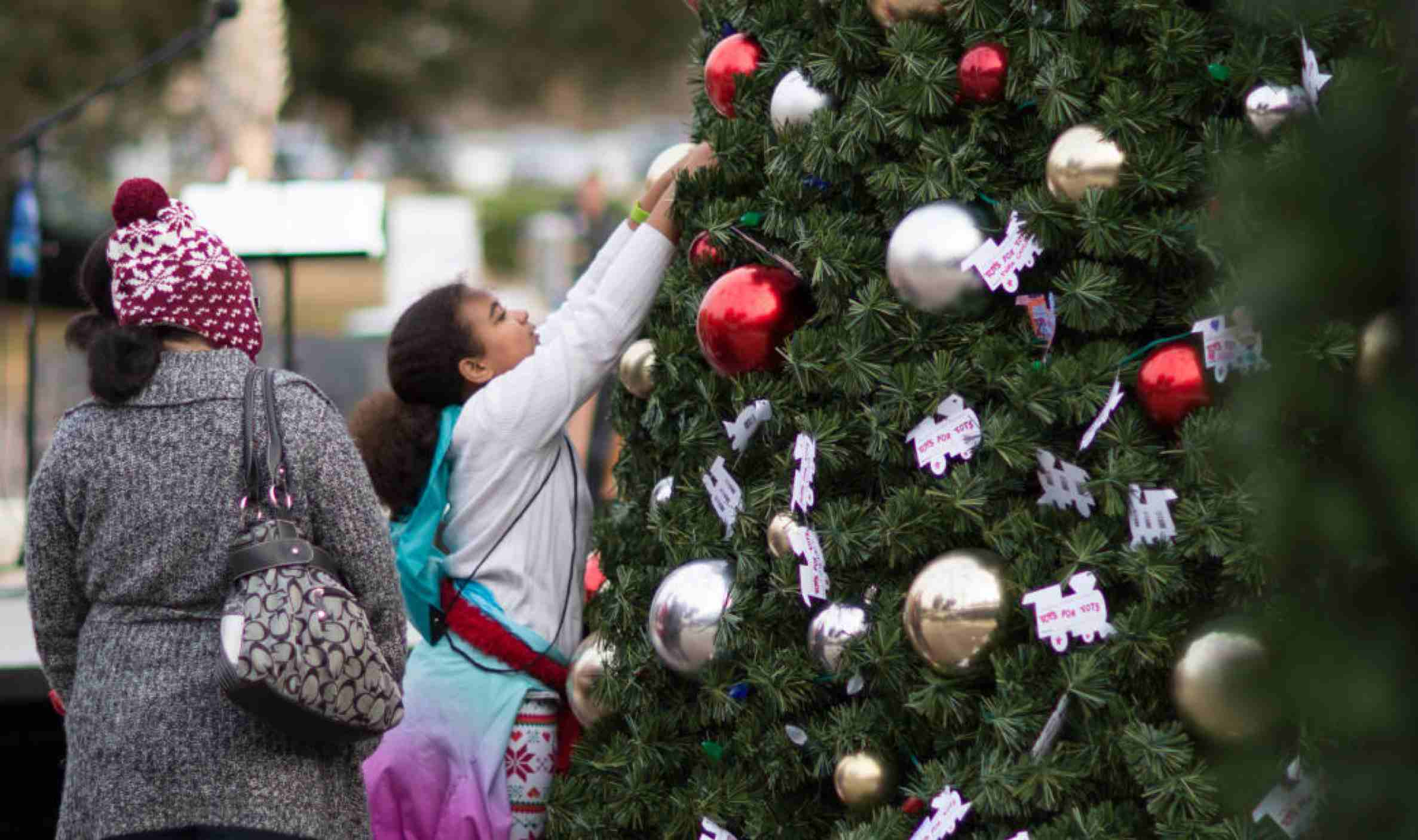 girl and her mother putting an ornament on a Toys for Tots christmas tree at the Myrtle Beach Christmas Towne