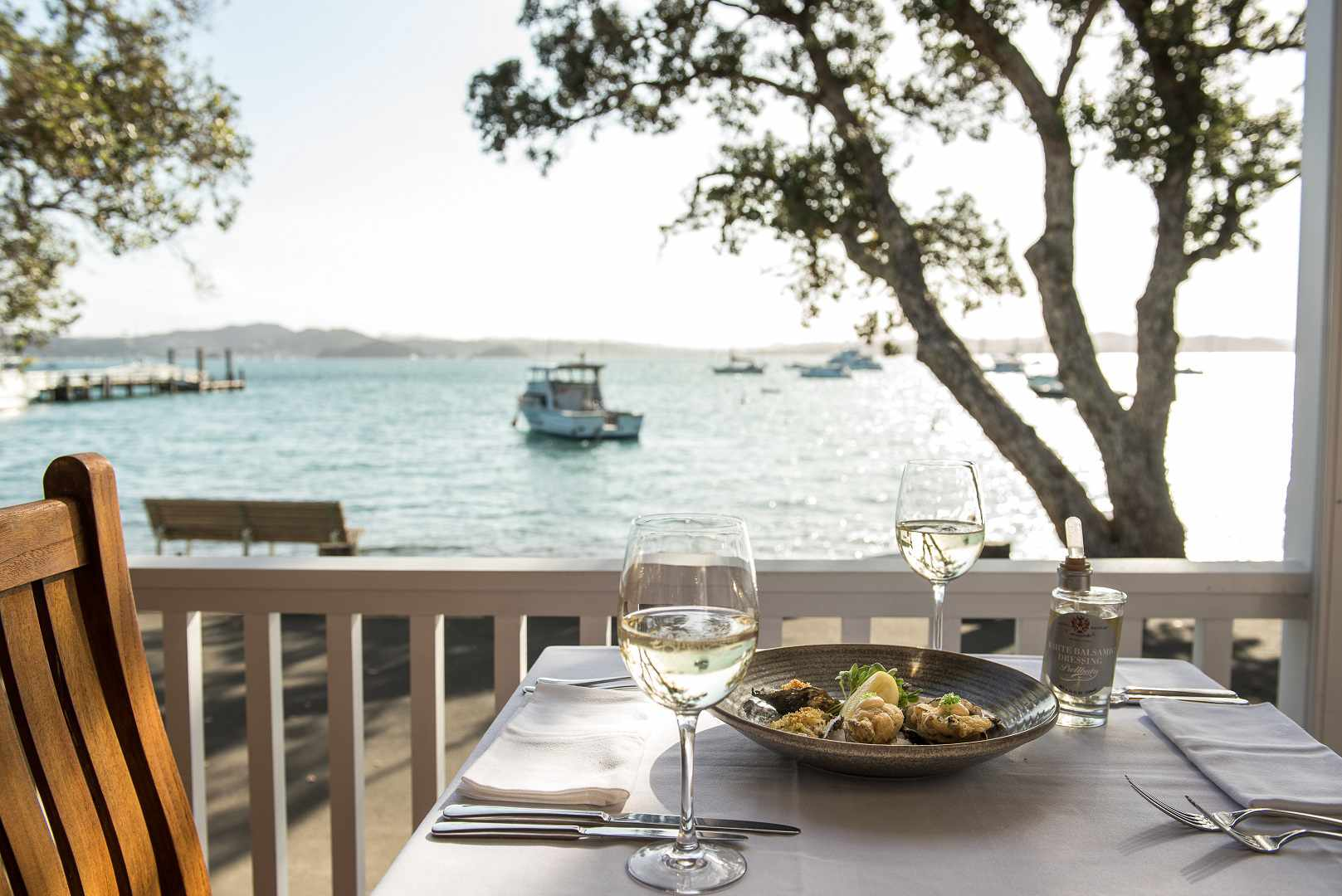 Two glasses of white wine and a plate of clame on a set table with views of boats on the water in the background. Take at Duke of Marlborough Hotel