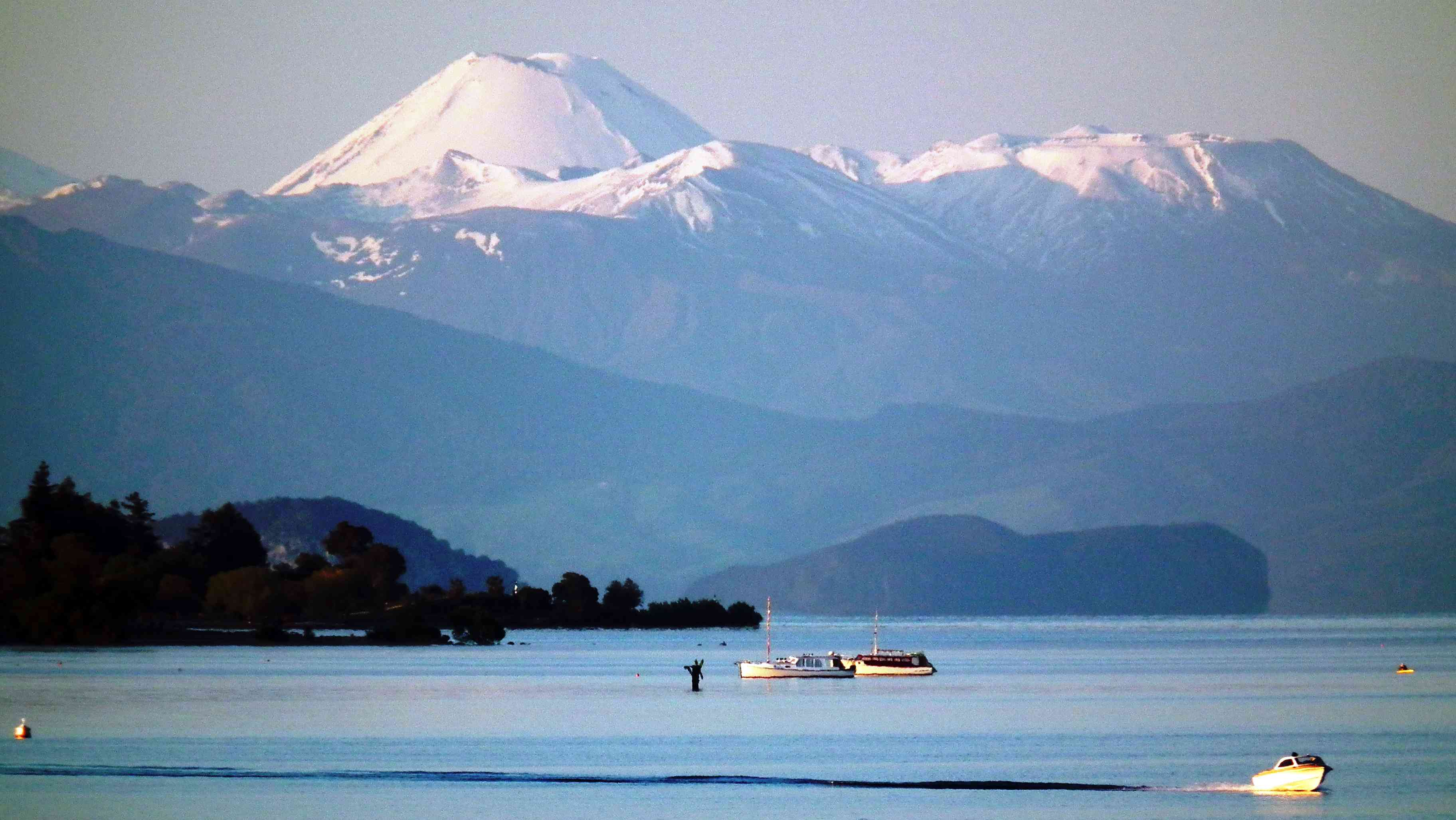 snowy mountains with a lake and boats in foreground