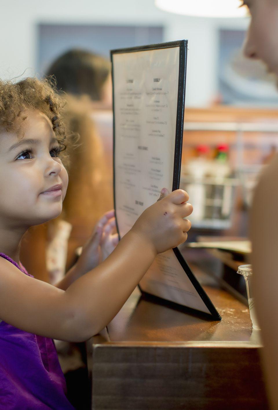kid looking at restaurant menu