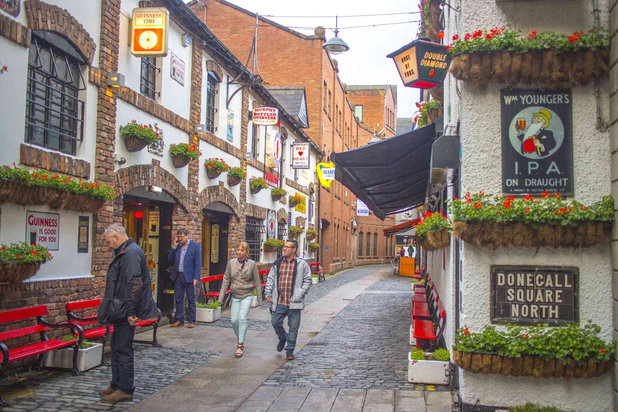 The pub-filled Cathedral Quarter in Belfast with four people walking on the street