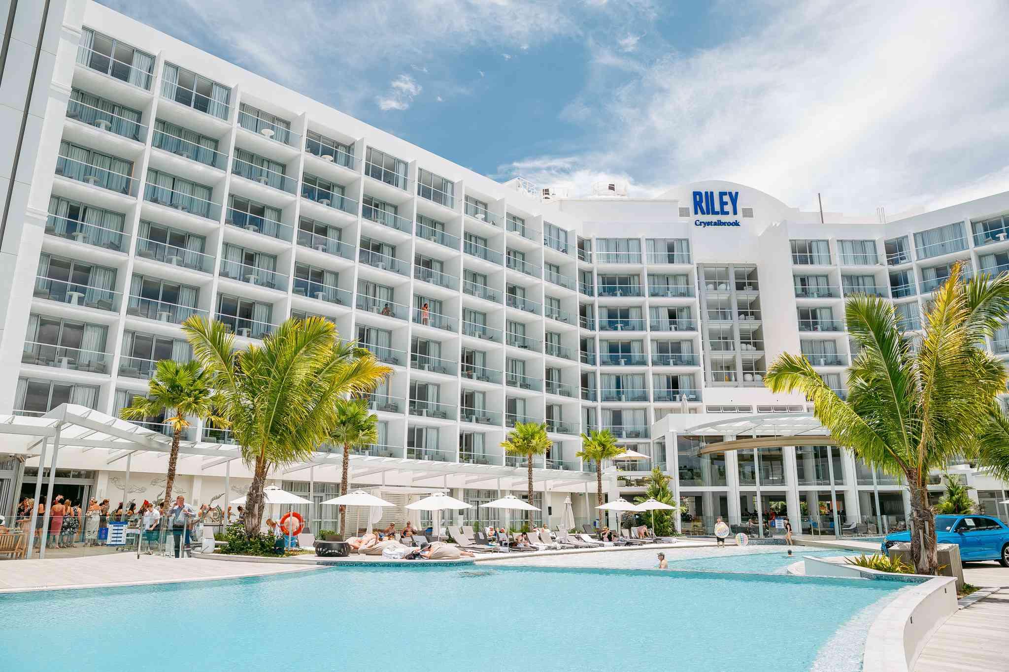 Área de piscina del Riley Resort con palmeras verdes