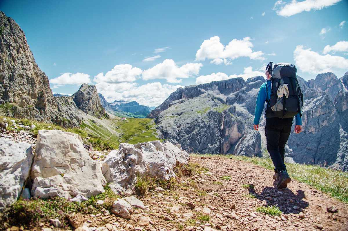 A backpacker hikes a trail in northern Italy with the rocky Dolomite Mountains in the background.