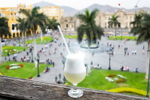 Pisco sour homemade cocktail with the background of the main square of Lima