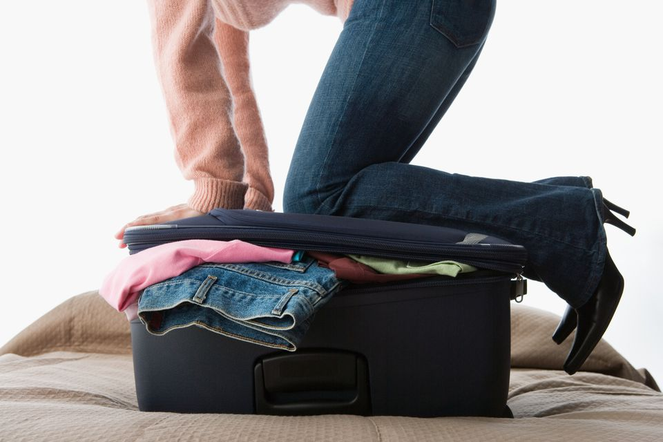 A woman kneeling on a suitcase full of clothes