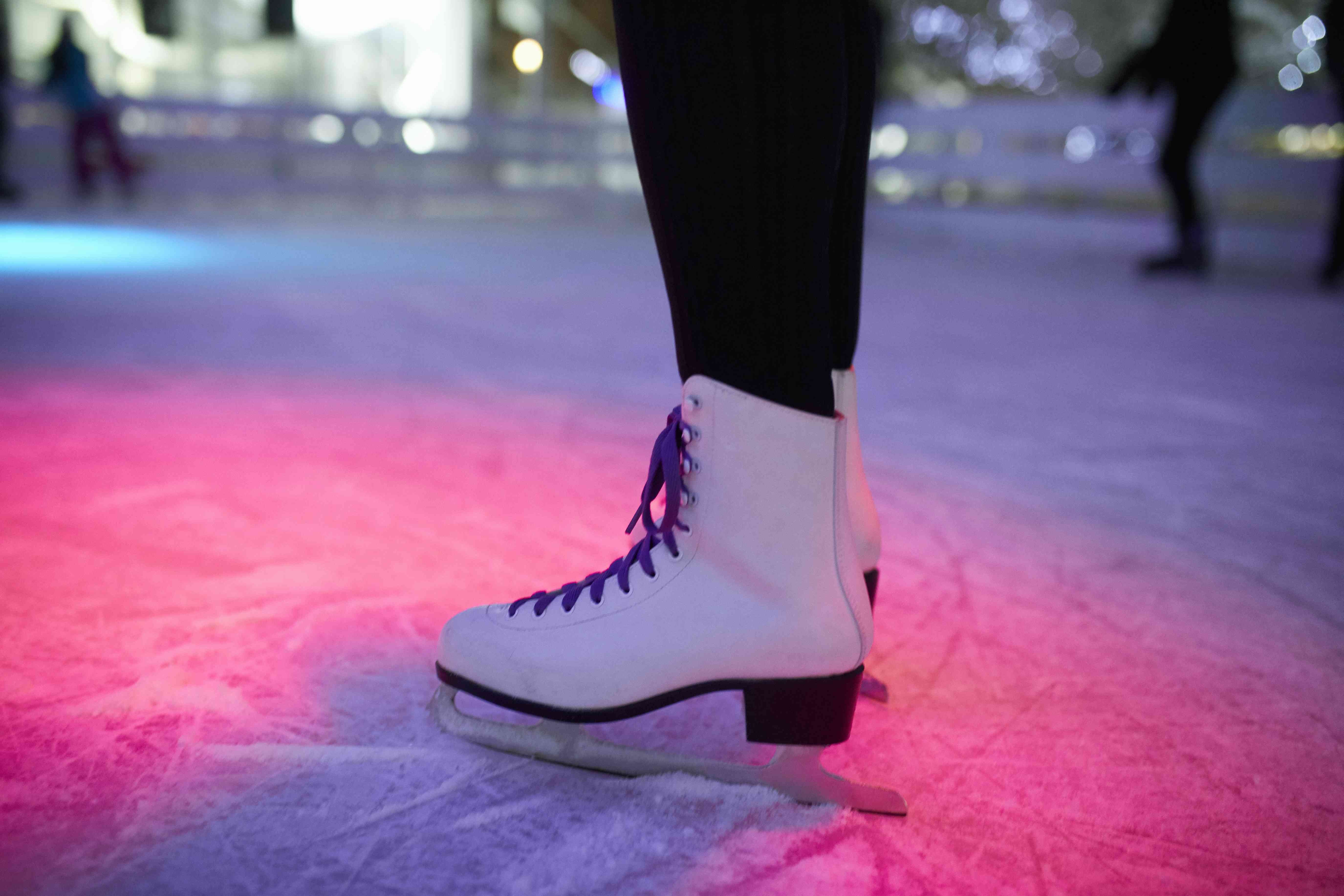 Leg of woman wearing ice skates standing on an ice rink