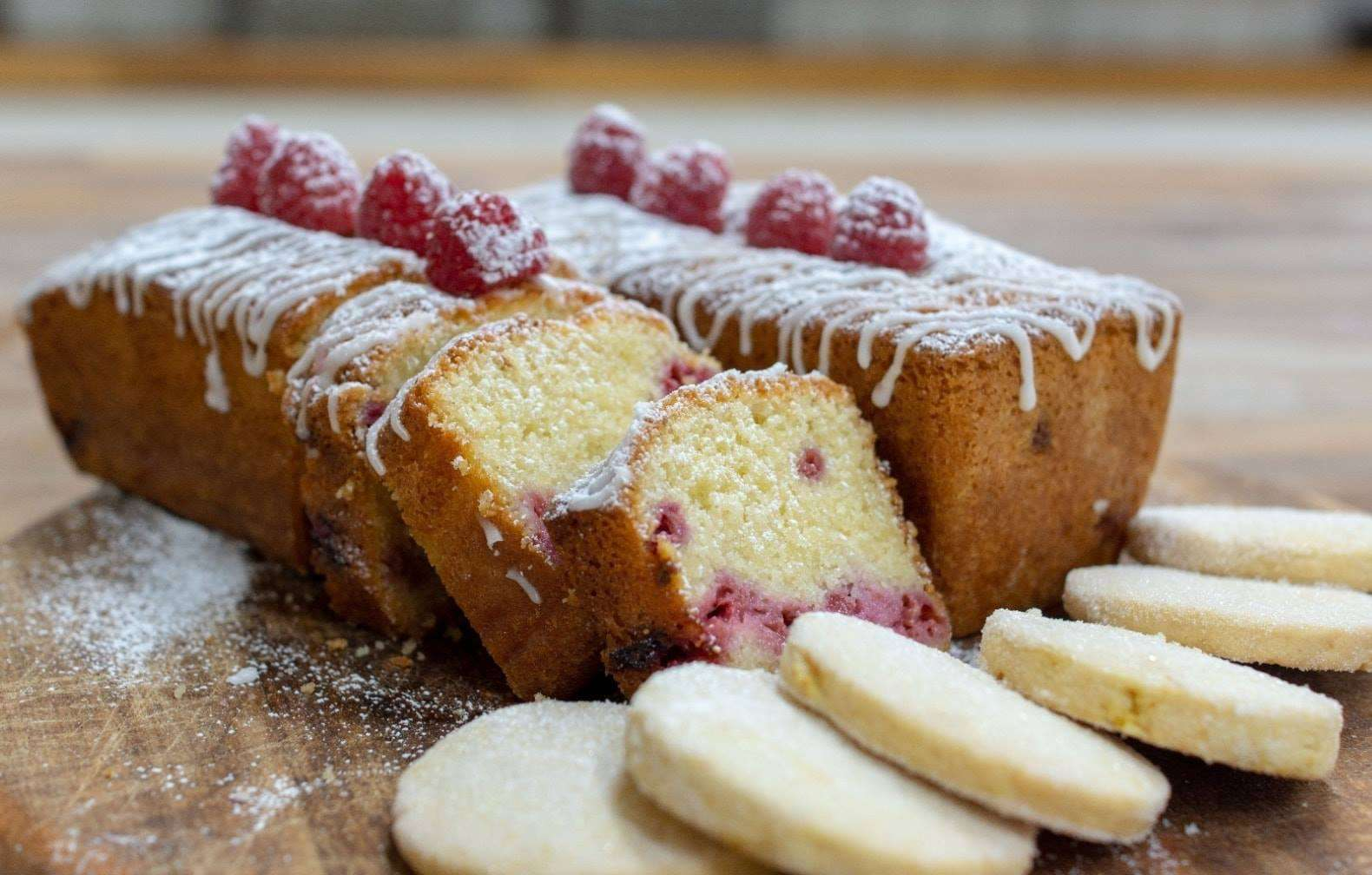 Two loaves of cranberry pound cake on a cutting board with six sugar cookies. One loaf has three slices cut from it