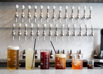 Five drinks in different sized beakers with a bunch of