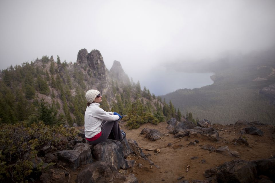 woman rests after hiking around the rim of Newberry Volcano