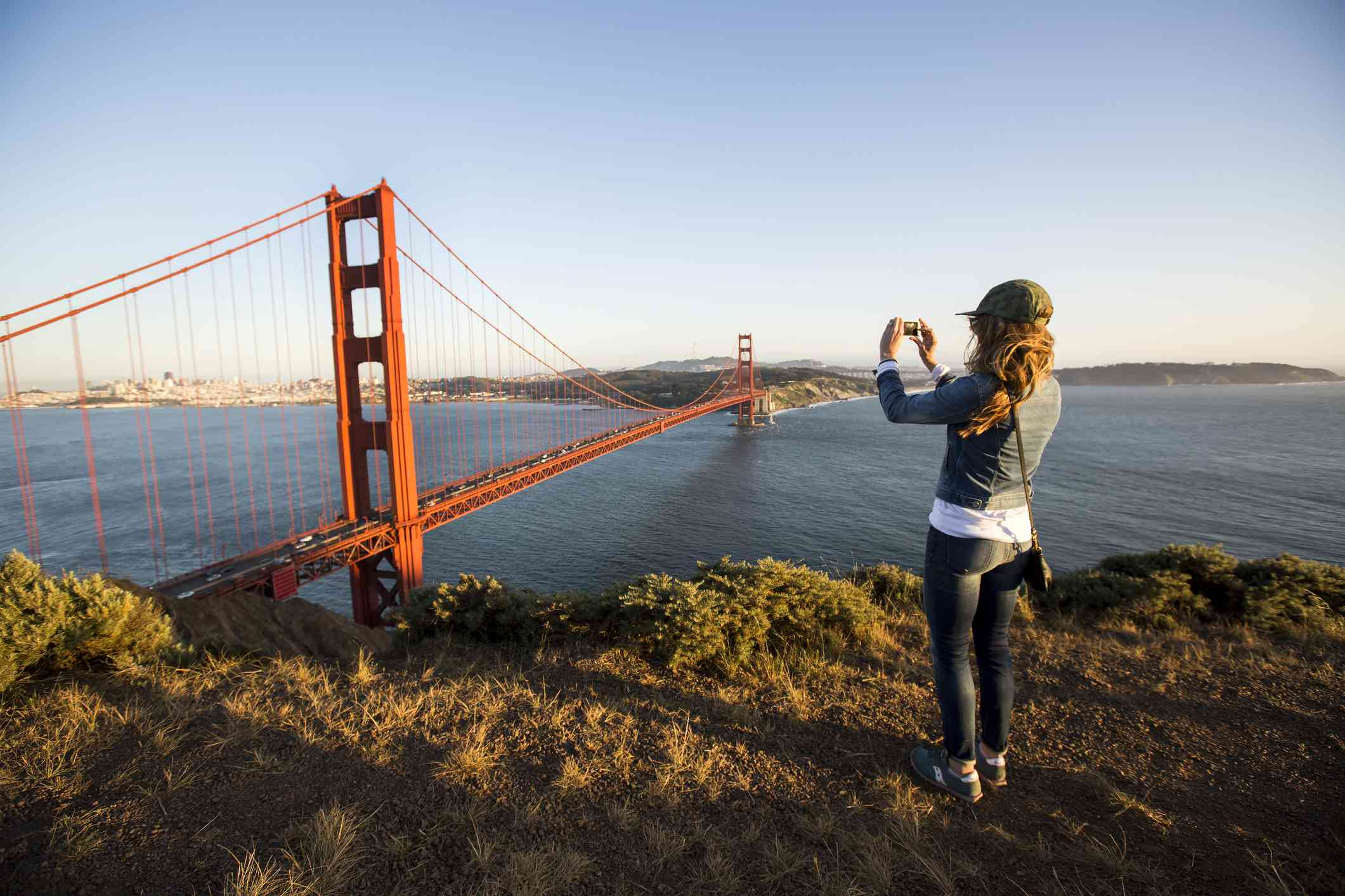 A woman taking a photo of the Golden Gate Bridge near sunset.