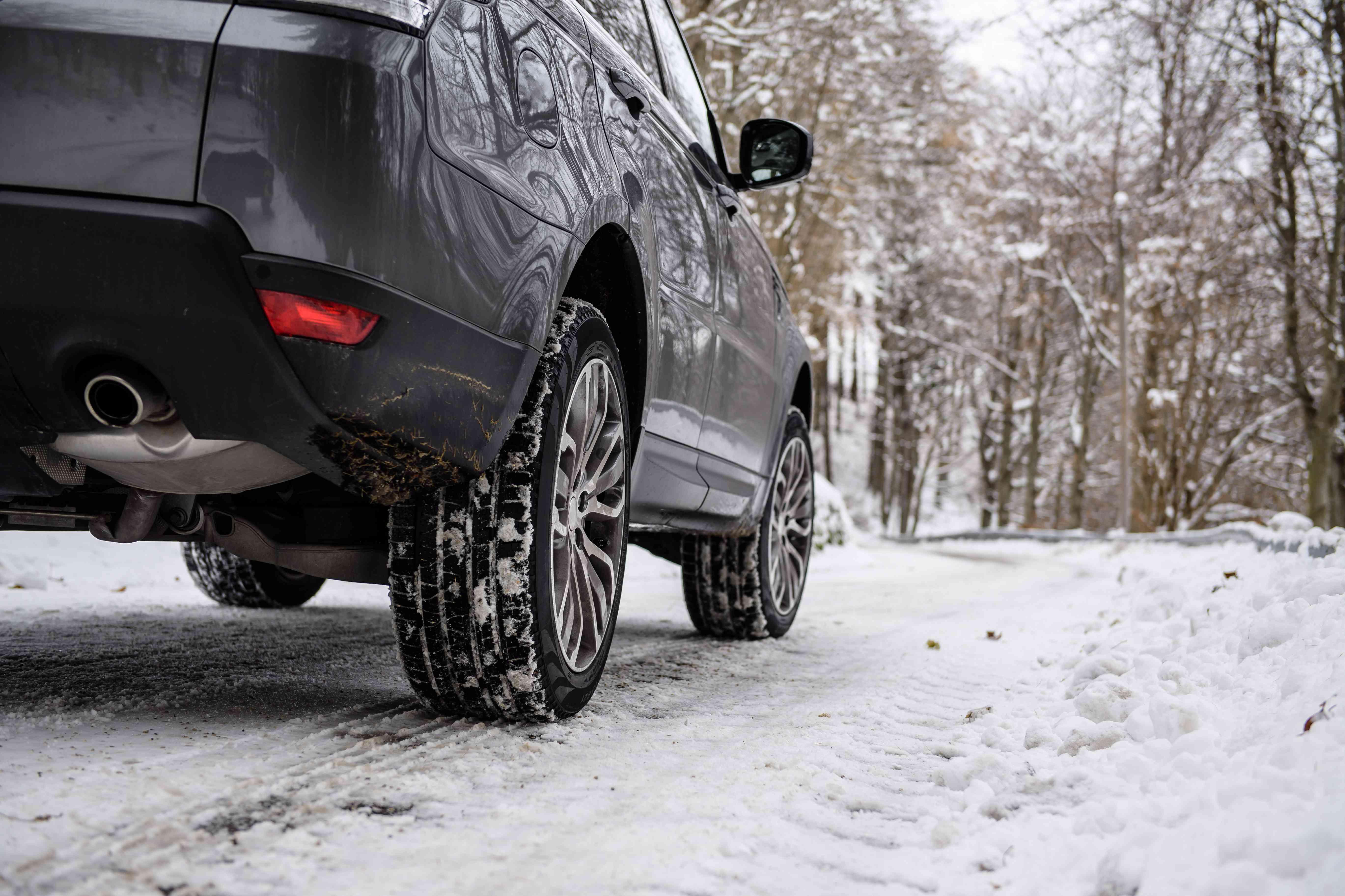Primer plano de neumáticos de invierno montados en un vehículo deportivo utilitario