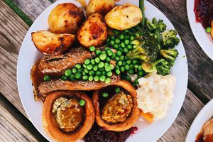 Traditional British Sunday roast dinner with chicken, vegetables, gravy and a Yorkshire pudding