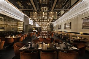 Restaurant dining room with dark tables, plush chairs, glass light fixtures and a mirrored ceiling