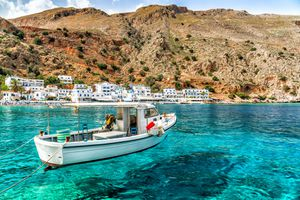 Boat in turquoise blue waters off the coast of Crete with white buildings and a mountain in the distance