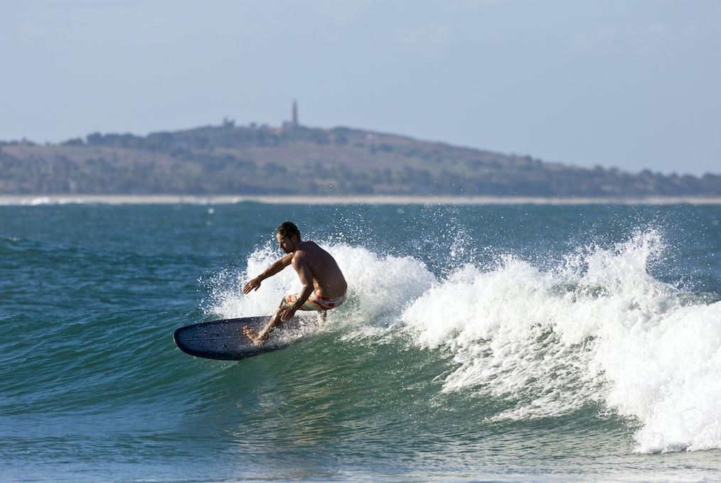 A surfer rides a wave off the coast of Mozambique