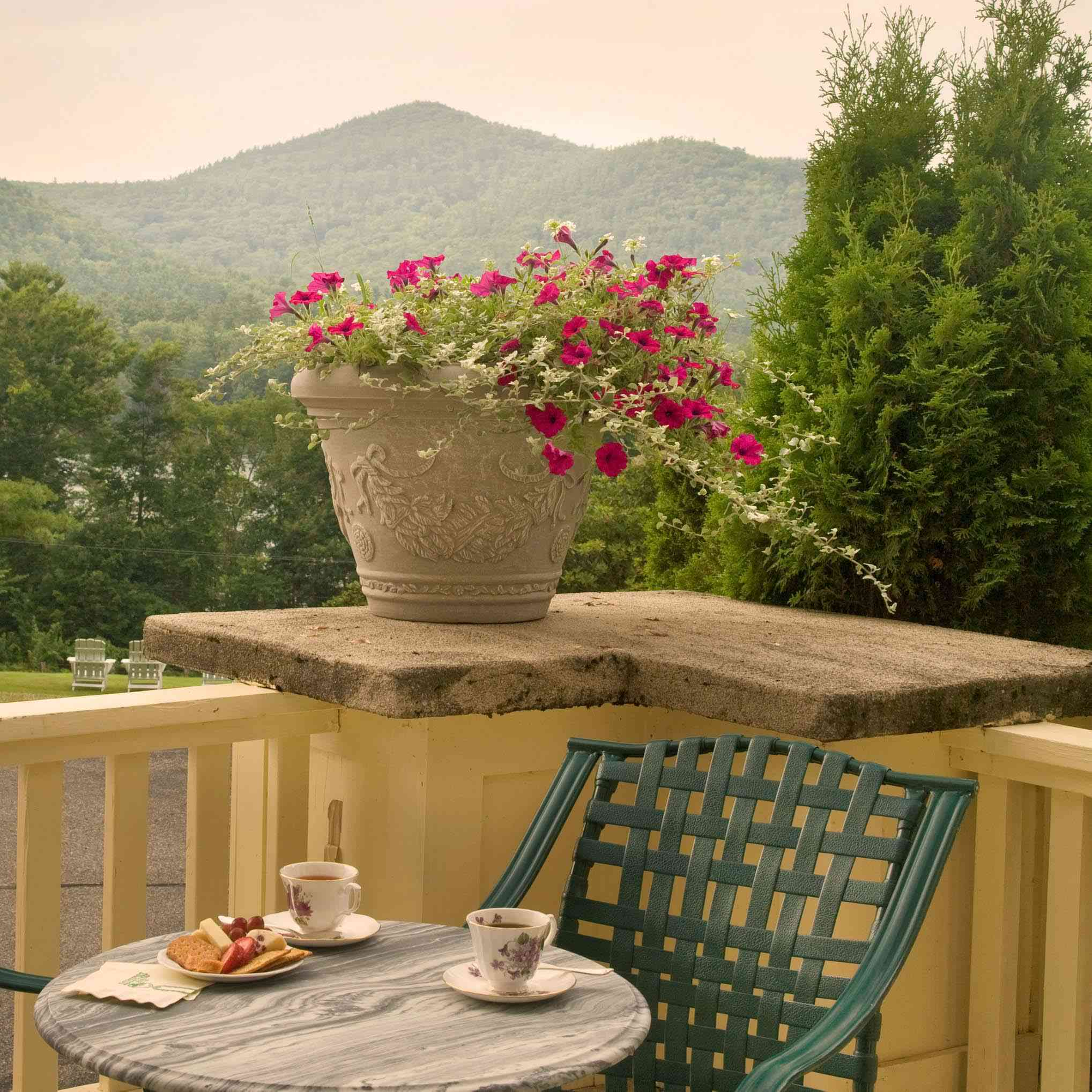 A chair on a patio overlooking mountains