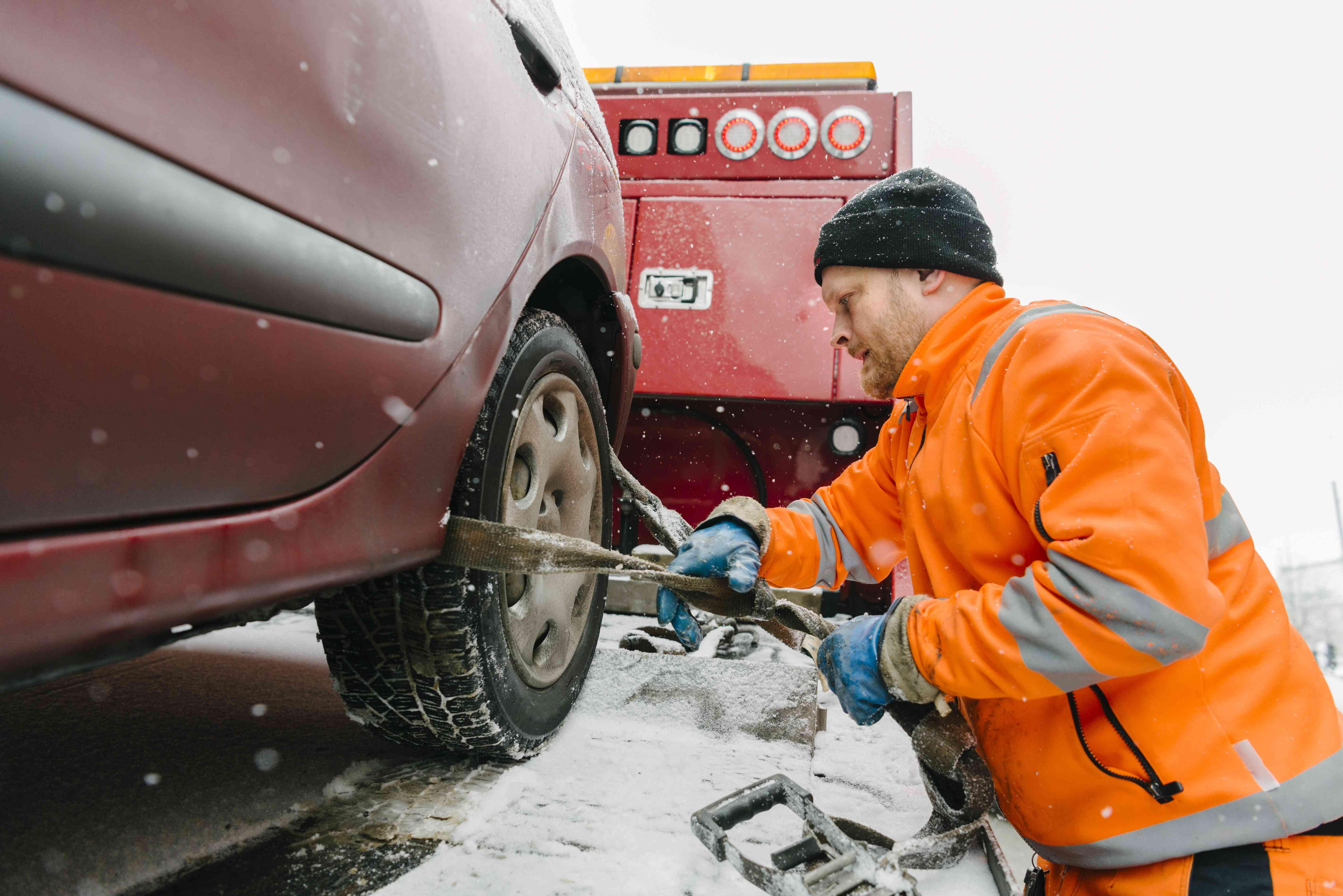 Vista lateral del conductor que coloca el neumático del automóvil con el equipo remolcado camión