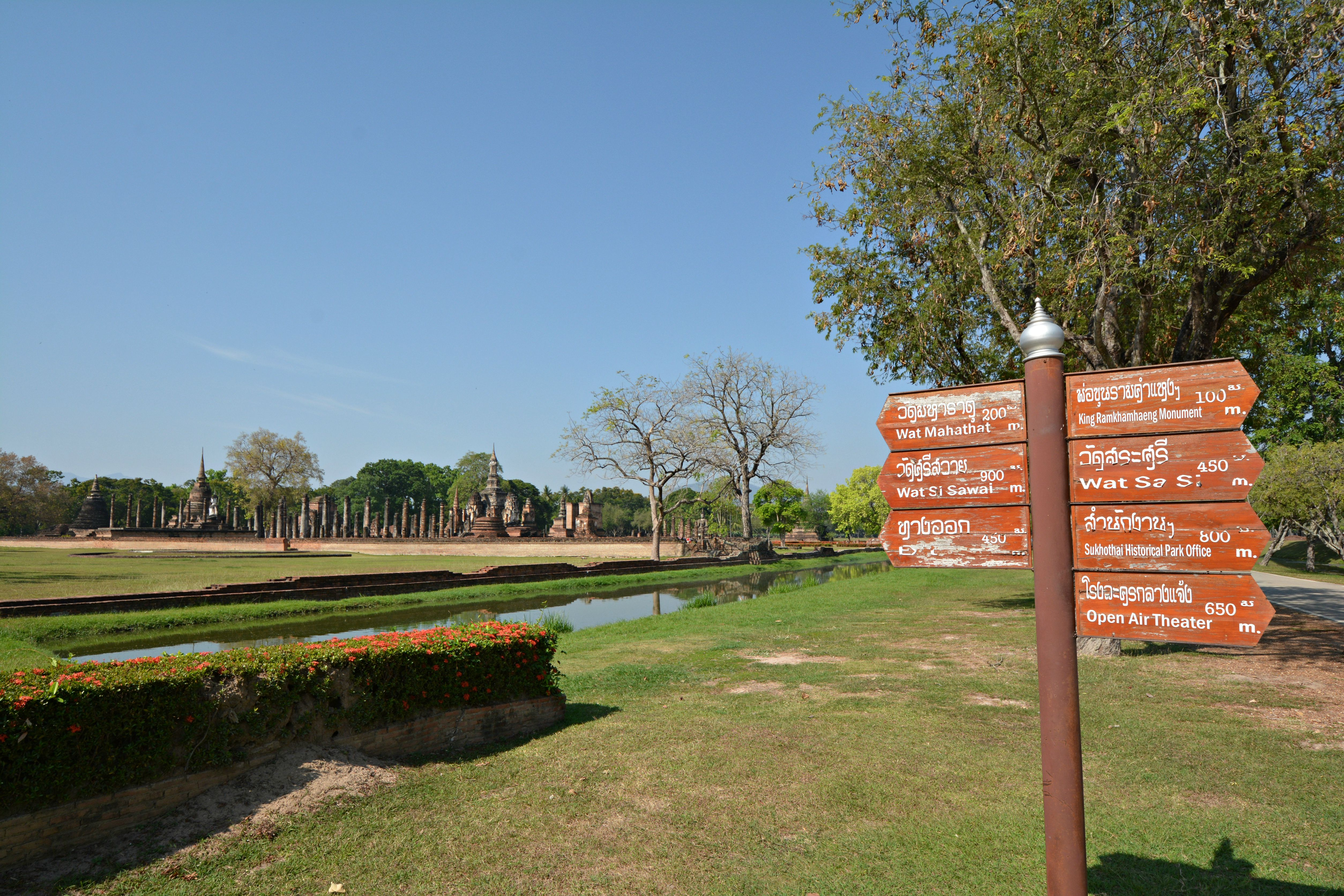 A sign and ruins in Sukhothai, Thailand