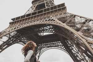 Woman Standing In Front Of Eiffel Tower