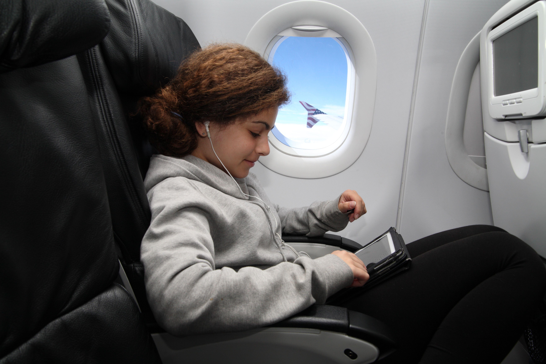 Chica en una tableta mientras vuela