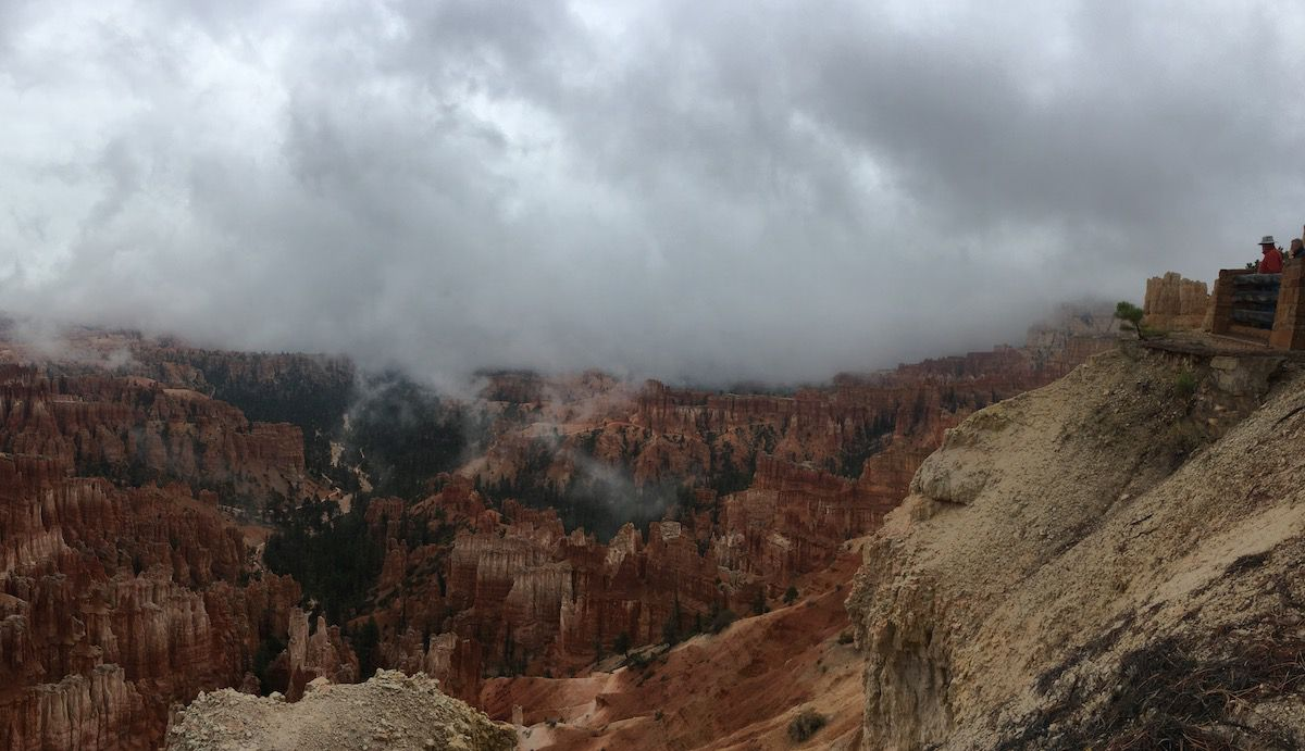 The red landscape of Bryce Canyon with dramatic clouds overhead.