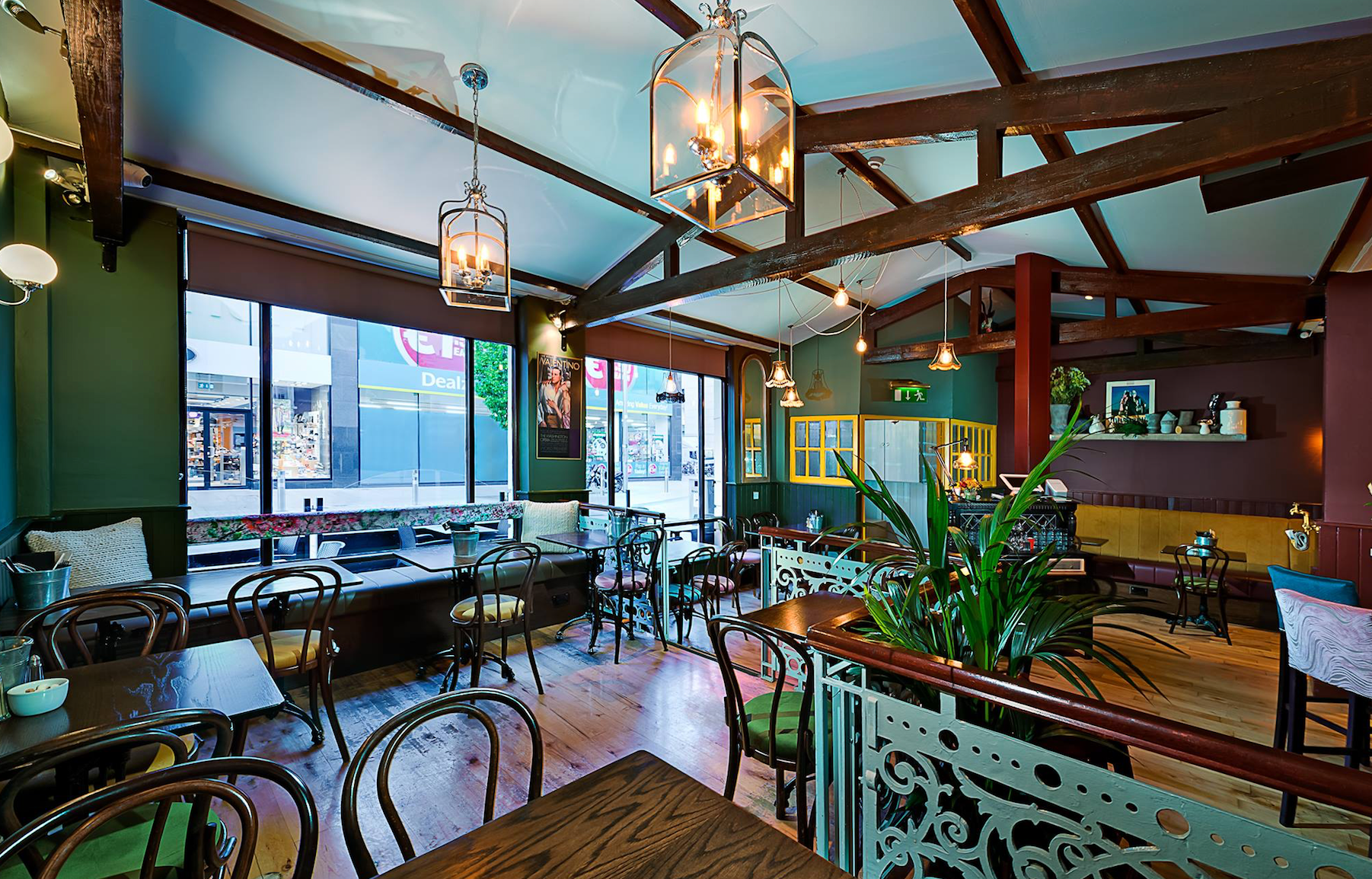 Green interior of restaurant with wood beam ceiling