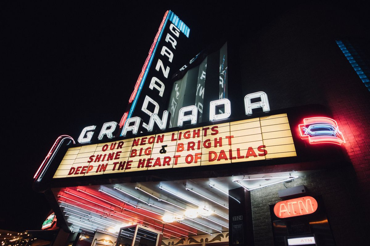 Low angloe of the Granada Theater signs and marquee at night. The marquee reads