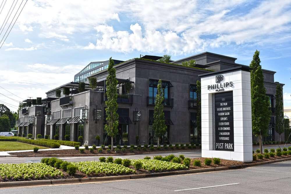 Centro comercial gris oscuro con jardines verdes y un letrero en blanco y negro